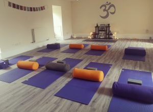shambhala yoga studio with yoga mats, blocks and bolsters laid out ready for class