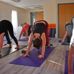 students doing downward dog in yoga class