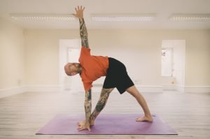 man doing warrior forward fold twist on yoga mat
