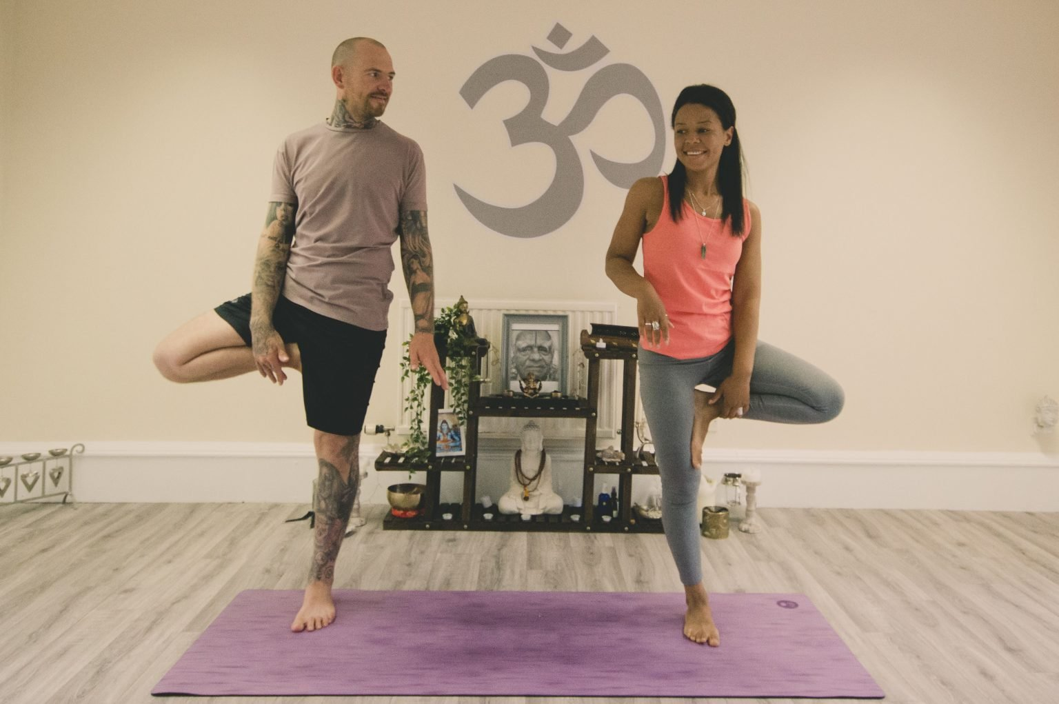 man and woman in standing tree pose side by side on yoga mat